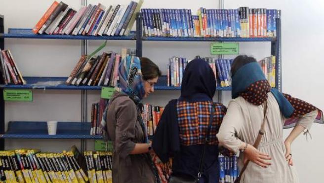 Mujeres iraníes miran los libros expuestos en una estantería durante la Feria Internacional del Libro de Irán, en Teherán.