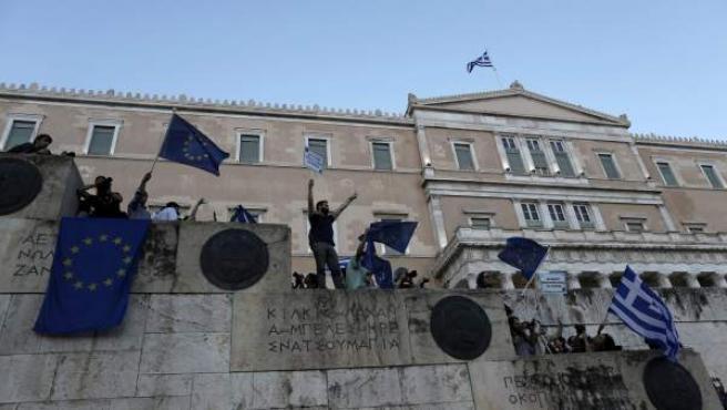 Manifestantes ondean banderas griegas y de la UE exigiendo que Grecia permanezca en la eurozona a las afueras del parlamento griego en Atenas.