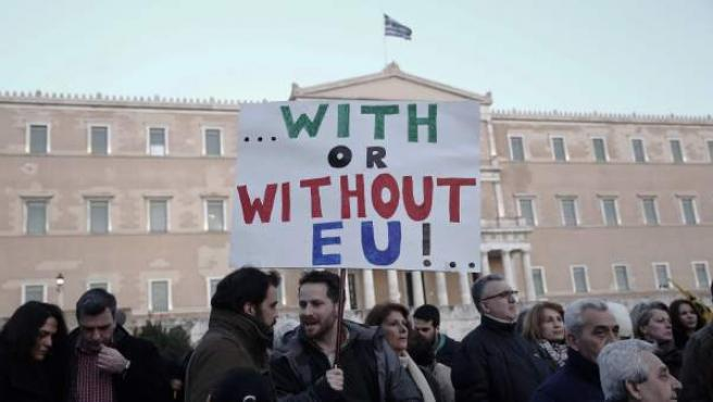 """Manifestantes griegos frente al parlamento heleno en Atenas con una pancarta que dice: """"Con o sin la UE""""."""