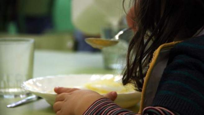 Una niña toma el almuerzo en un comedor escolar.