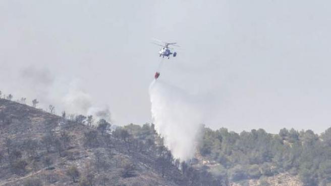 Cuatro helicópteros y medios terrestres trabajan en la extinción de un incendio forestal declarado en el puerto murciano del Garruchal, al que se dirigen efectivos de la Unidad Militar de Emergencias (UME) de Bétera (Valencia) y dos aviones del Ministerio de Agricultura, Alimentación y Medio Ambiente.