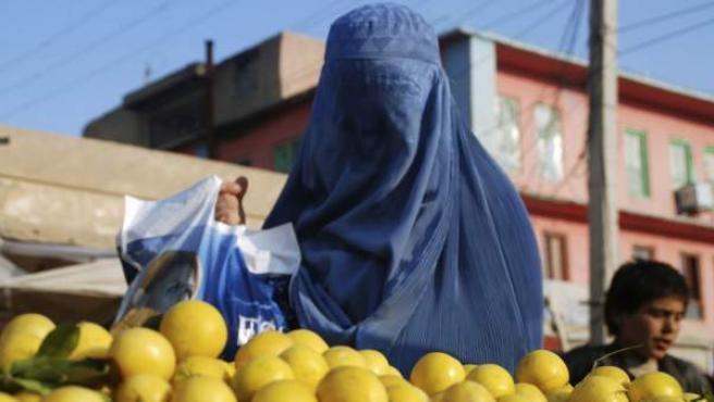 Una mujer afgana con burka compra limones en un puesto de fruta callejero en Mazar-e-Sharif, Afganistán.