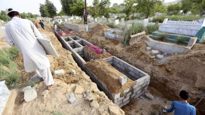 Trabajadores del cementerio preparan los nichos para los fallecidos durante la ola de calor en Karachi, Pakistán hoy 25 de junio de 2015.