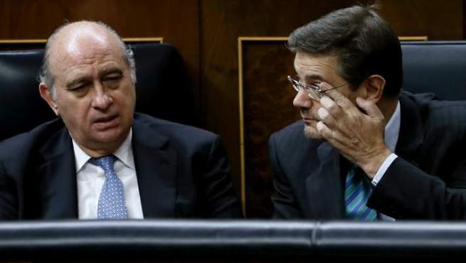 Combo de fotografías del ministro de Interior, Jorge Fernández (i), y el de Justicia, Rafael Catalá (d), que conversan durante la sesión plenaria en el Congreso de los Diputados.