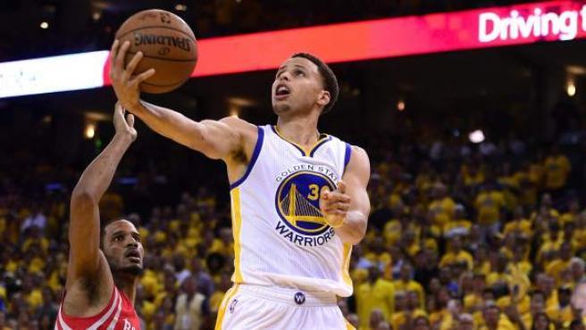 El base Stephen Curry y el reserva Shaun Livingston surgieron como los líderes encestadores de los Warriors de Golden State que completaron una remontada de 16 puntos y vencieron 110-106 a los Rockets de Houston en el primer partido de las finales de la Conferencia Oeste, que disputan al mejor de siete. En la imagen, Curry entra a canasta, observado por Trevor Ariza.