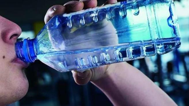 Una persona bebiendo agua embotellada.