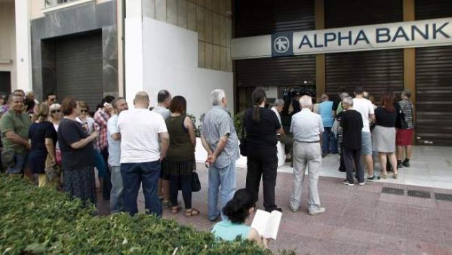 Largas colas ante los cajeros del Alpha Bank en Atenas, Grecia.