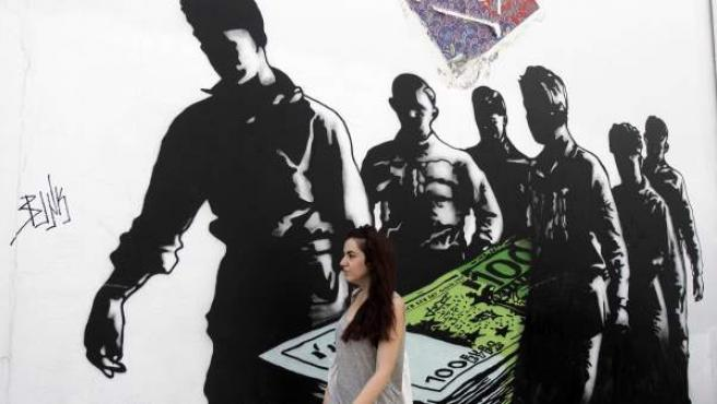 """Una mujer pasa junto a un grafiti titulado """"La muerte de los euros"""" en Atenas (Grecia)."""