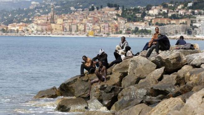 Varios inmigrantes esperan en la playa de la ciudad fronteriza con Italia de Menton, Francia.