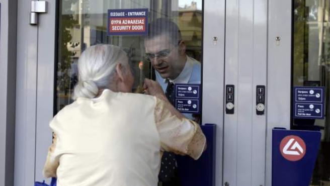 Una mujer pensionista habla con el encargado de un banco en Atenas, Grecia, para pedirle información sobre el control de capitales.