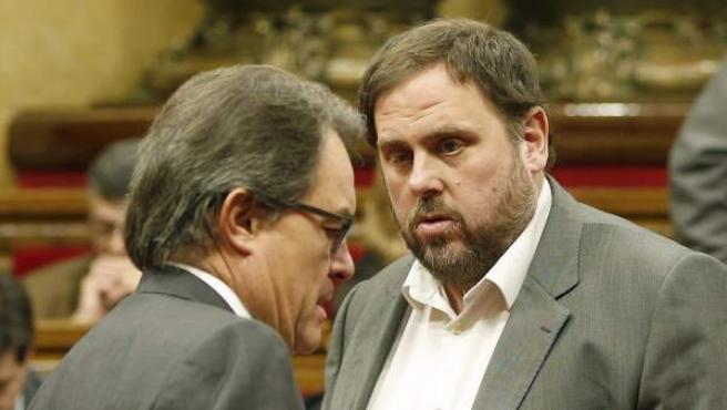 El presidente de la Generalitat, Artur Mas, y el líder de ERC, Oriol Junqueras, conversan en el hemiciclo del Parlamento catalán.