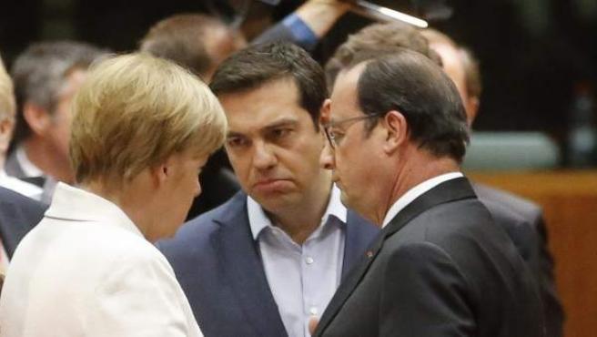 La canciller alemana, Angela Merkel, habla con el presidente francés, François Hollande, y el primer ministro griego, Alexis Tsipras, en la cumbre extraordinaria de líderes de los 19 países que comparten el euro.