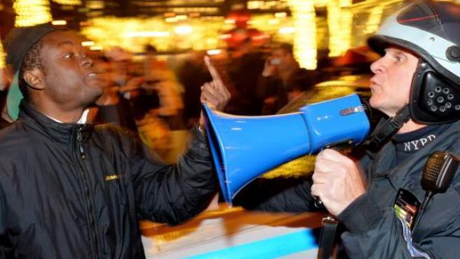 Un manifestante discute con un policía en una protesta contra la decisión del gran jurado del barrio neoyorquino de Staten Island de no presentar cargos contra el policía que presuntamente causó la muerte de Eric Garner, un ciudadano afroamericano mientras era detenido, en Nueva York (EE UU).