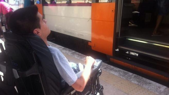Cristian ante el tren en la estación de El Vendrell (Tarragona), al que no puede subir con su silla de ruedas por no estar adaptados los convoyes.