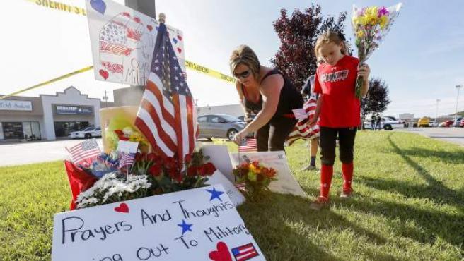 Una familia deja flores en un memorial instalado cerca al edificio de reclutamiento militar de EE UU este jueves 16 de julio de 2015 tras el tiroteo en Chattanooga (Tennessee, EE UU) en el que murieron cuatro infantes de marina.
