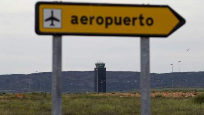 Un cartel señala la entrada al Aeropuerto Central de Ciudad Real. Al fondo, la torre de control del aeropuerto.