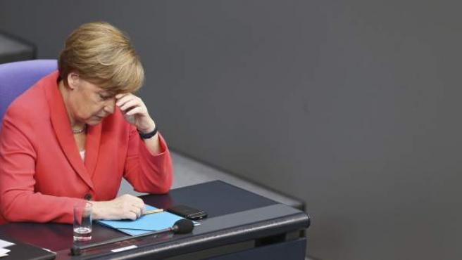 La canciller alemana, Angela Merkel, reacciona durante la intervención de la oposición durante una sesión extraordinaria del Bundestag (cámara baja alemana).