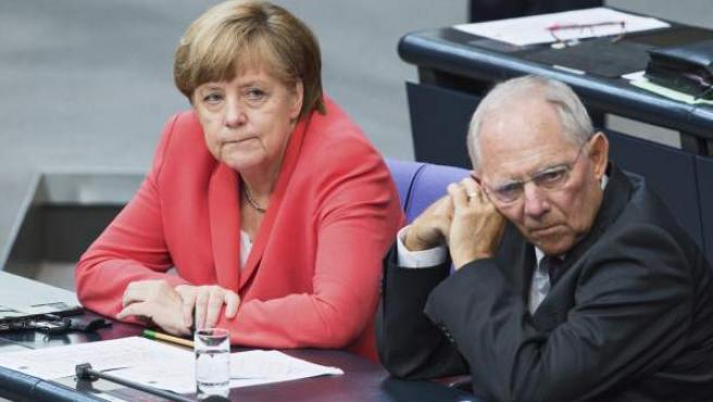 El ministro de Finanzas alemán, Wolfgang Schäuble (d), y la canciller alemana, Angela Merkel, durante una sesión extraordinaria del Bundestag en la que se votó la autorización a su Gobierno para la apertura de las negociaciones destinadas a acordar un tercer paquete de rescate para Grecia, en Berlín (Alemania).