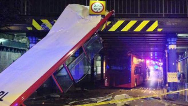 Imagen de un autobús de dos pisos que sufrió un accidente en Londres y perdió el techo al chocar con un puente, dejando siete heridos leves.
