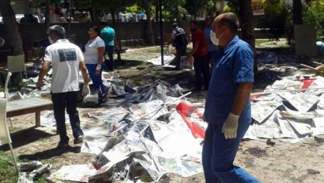Un médico pasa junto a varios cadáveres cubiertos con periódicos en Suruç, al sureste de Turquía, donde ha habido un atentado suicida.