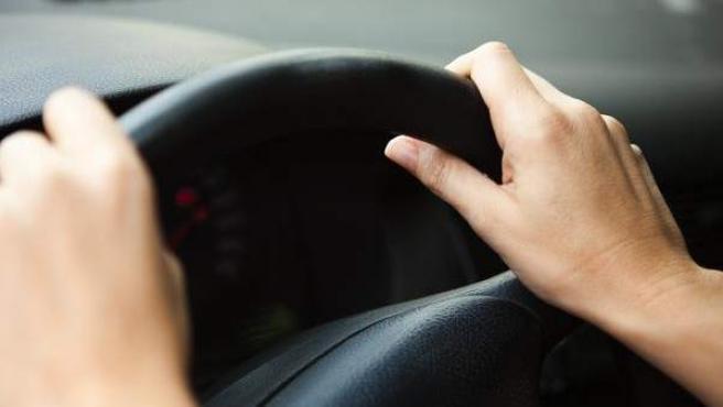 Una persona, al volante en su coche.