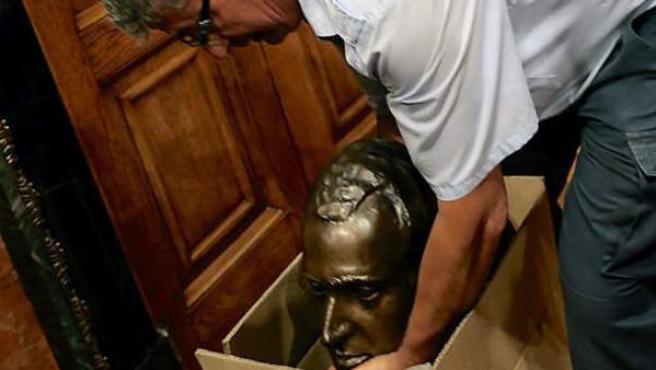 Un operario guarda en una caja de cartón el busto del rey Juan Carlos I que había en el salón de plenos del Ayuntamiento de Barcelona.