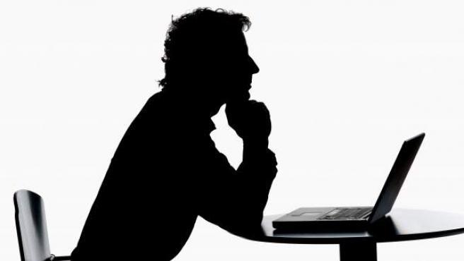 Un hombre trabaja con su ordenador portátil.