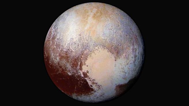 """Imagen facilitada por la NASA de Plutón, con colores falsos que ensalzan la belleza del planeta enano. La misión New Horizons continúa descubriendo los misterios de Plutón. Según explican los expertos, 10 días después de la aproximación máxima, el perfil del planeta es muy diferente al que pensaban. Hielos que fluyen, una química exótica en su superficie, cordilleras y una vasta neblina, son algunas de las """"sorpresas"""" que se ha llevado el equipo de la misión."""