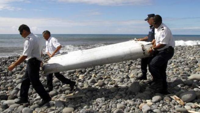 Varios policías llevan el resto de un avión no identificado en La Reunión.