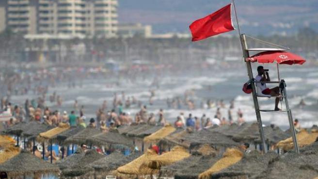 Un socorrista vigila la playa de la Malvarrosa (Valencia) a la que ha acudido un gran número de personas a pesar de la inestabilidad climática, señalada con la bandera roja.