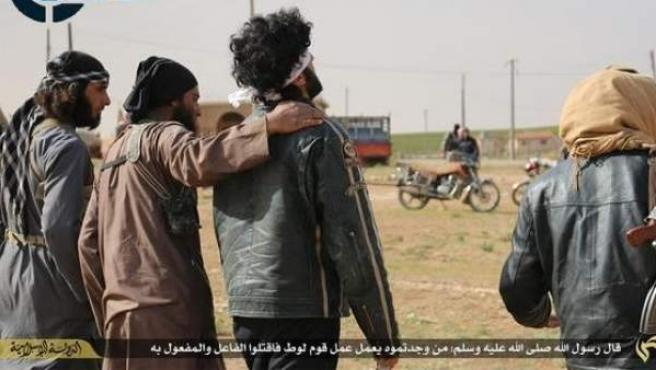 Militantes de Estado Islámico en Siria abrazando a dos prisioneros antes de lapidarlos por ser homosexuales.