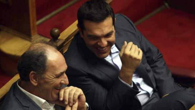 Tsipras (dcha), conversa con el ministro de Economía, Infraestructura, Comercio y Turismo, George Stathakis (izda), durante la sesión parlamentaria en Atenas