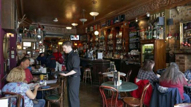Un camarero atiende a unos clientes en el interior de un establecimiento, en una imagen de archivo.