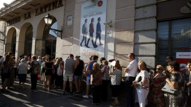 Numerosas personas guardan cola a la entrada del Teatro La Latina.