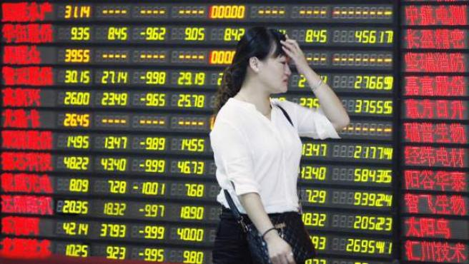 Una inversora pasa delante de una pantalla que muestra información bursátil en una compañía de compraventa de acciones en Huaibei, provincia de Anhui (China) este 24 de agosto de 2015.