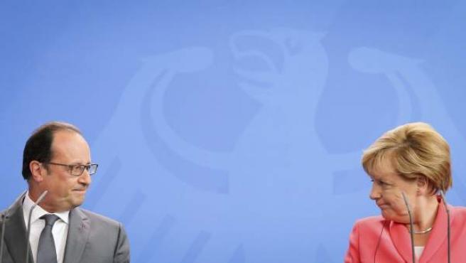 La canciller alemana, Angela Merkel (dcha), y el presidente galo, François Hollande (izda), ofrecen una rueda de prensa en la Cancillería en Berlín (Alemania).