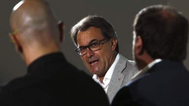 Los candidatos de Junts pel Sí Raul Romeva (i) y Oriol Junqueras (d) escuchan al president de la Generalitat y candidato numero 4 de Junts pel Sí, Artur Mas (c), durante el acto de presentación del programa electoral de la coalición.