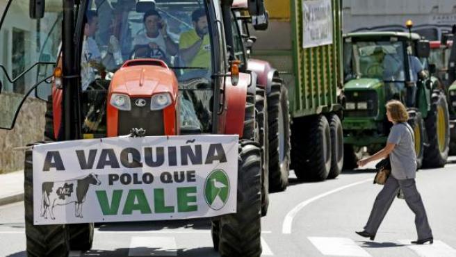 """Un tractor con la pancarta """"la vaca por el precio que vale"""", en la concentración y posterior marcha por la ciudad, de ganaderos convocados por los principales sinicatos agrarios para protestar por la situación que vive el sector por los bajos precios de la leche, esta mañana en Santiago de Compostela."""