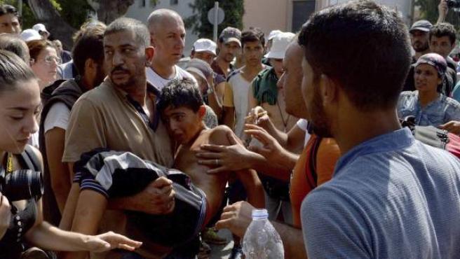 Refugiados llevan en brazos a un niño que se desmayó durante la larga espera para el procedimiento de registro en el puerto de Mitilene en la isla grieva de Lesbos.
