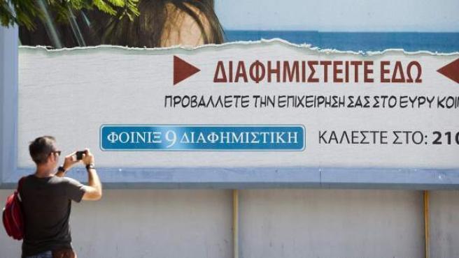 Un hombre fotografía la cartelería publicitaria instalada en algunas calles de Santa Cruz de Tenerife para convertir a la capital tinerfeña en la Atenas contemporánea, con motivo del rodaje de la película Bourne 5.