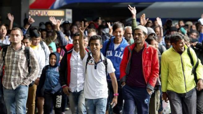 Varios refugiados saludan a su llegada a la estación de tren de Munich.