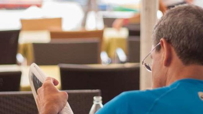 Un cliente lee el periódico mientras desayuna en una terraza de Las Canteras