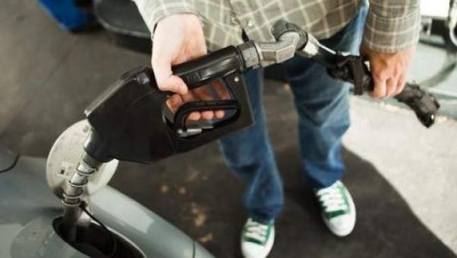Un hombre llena su tanque de gasolina en una estación de servicio.