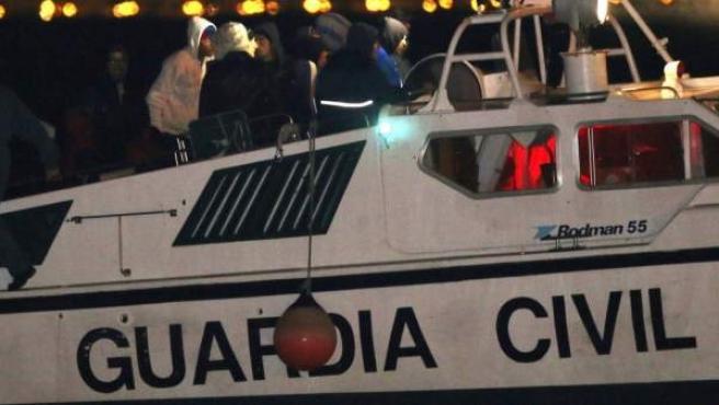 Efectivos de la Guardia Civil trasladan al puerto de Almería a catorce inmigrantes interceptados cuando viajaban en una patera.