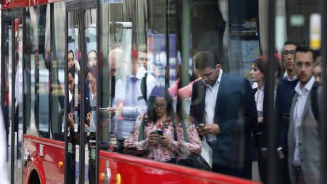 Una foto de trabajadores esperando para subir al autobús que los lleve al trabajo.