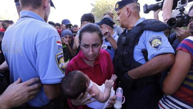 Refugiados intentan abrirse paso a través de la policía para registrarse tras cruzar la frontera con Serbia en Tovarnik, Croacia.