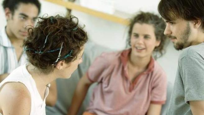 Un grupo de jóvenes mantiene una conversación informal.