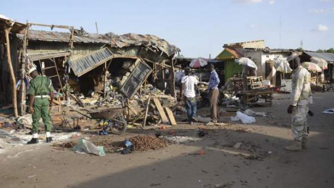 Varias personas observan el lugar de un ataque suicida con bomba en un mercado en Maiduguri, Nigeria, cometido supuestamente por Boko Haram.
