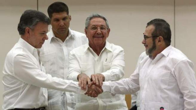 """El presidente de Cuba, Raúl Castro (cen), aprieta las manos del presidente de Colombia Juan Manuel Santos (izq) y el máximo líder de las FARC, Rodrigo Londoño (der), alias """"Timochenko"""" durante el acuerdo de paz alcanzado en material de justicia transicional."""