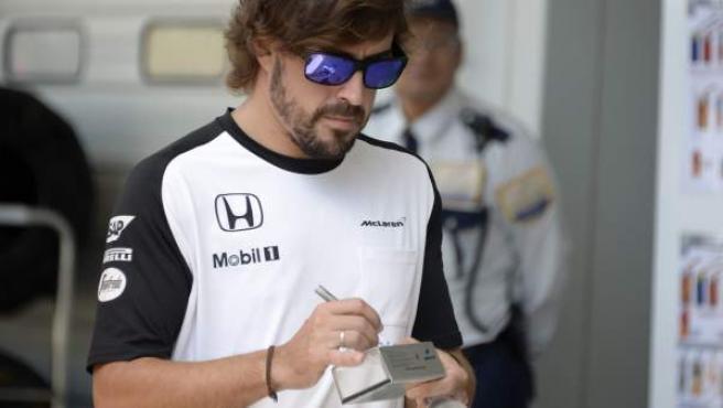 El piloto español Fernando Alonso firma un autógrafo en el circuito japonés de Suzuka.